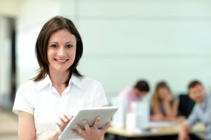 Office worker using electronic tablet in on front of group